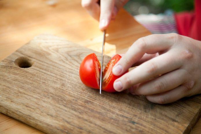 Разрезают томат