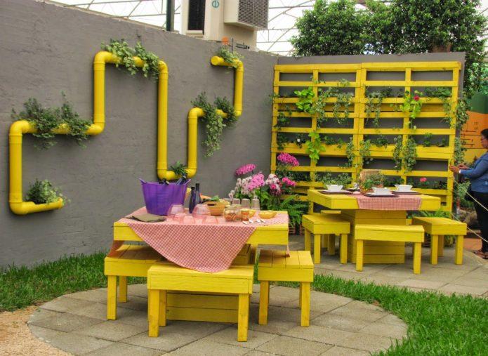 Жёлтая палетта, маскирующая стену забора