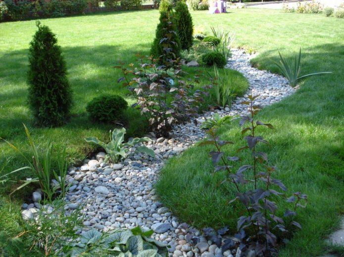 Сухой ручей из гальки в саду