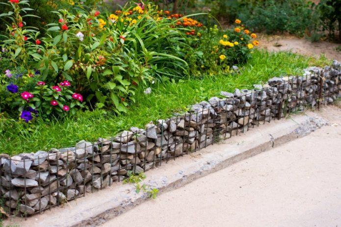 Цветник, огороженный сеткой с камнями