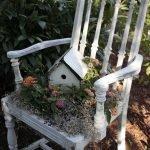Белый стул, на нём — домик, окружённый цветами