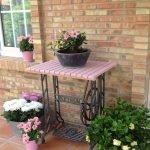 Столик от швейной машинки, на этом предмете мебели и с правой и с левой сторон от него стоят цветы в горшках