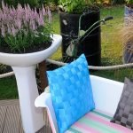 Растущие в раковине сиреневые цветы, рядом с предметом сантехники — кушетка с голубой и чёрной подушками