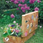 В чемодане, украшенном наклейками, растут цветы