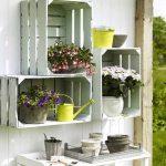 Ящики, прикреплённые к деревянной стене, с цветами в горшках