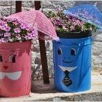 Розовое и голубое ведёрки с нарисованными на них лицами, цветы в ёмкостях