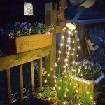 К носику лейки прикреплены гирлянды, которые красиво свисают и освещают растения в горшках