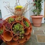 Фантастическая сфера-вазон из цветочных горшков с растениями в части из них