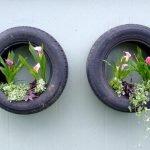 Цветы в висящих на стене покрышках от машин