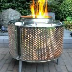 Барабан старой стиральной машины, из которого вырывается огонь
