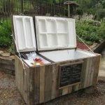 Холодильник, лежащий в горизонтальном положении, на даче; бутылки и лёд в одном из его отделений