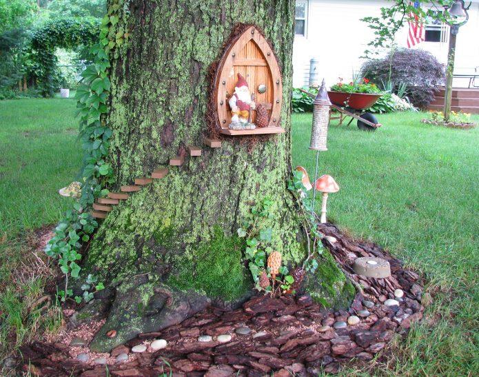 Ствол дерева, украшенный лестницей и дверцей