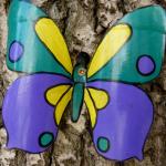 Бабочка из пластиковой бутылки на стволе дерева
