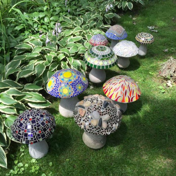 Разноцветные статуэтки в виде грибов на участке