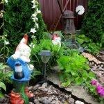 Гном из гипса и мельница в саду