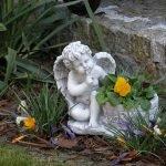 Небольшая гипсовая фигурка ангела в саду