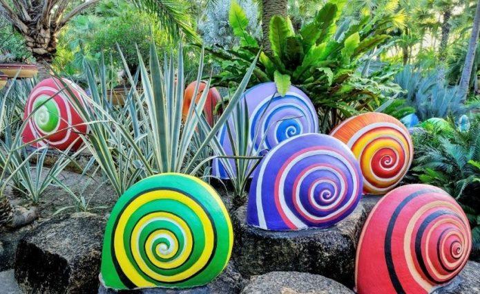 Разноцветные гипсовые улитки в саду