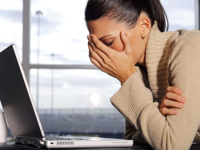 Уставшая женщина за ноутбуком