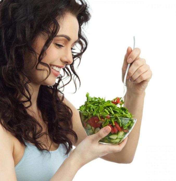 Девушка ест рукколу