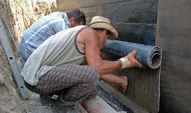 Строители оклеивают стену листами гидроизоляционного материала