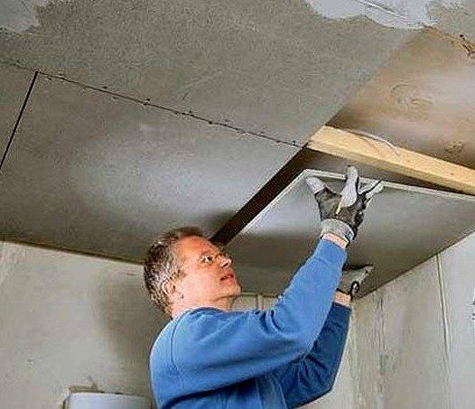 Строитель монтирует потолок из асбестоцементных плит