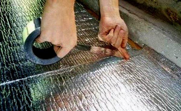 Руки склеивают листы утеплителя строительным скотчем