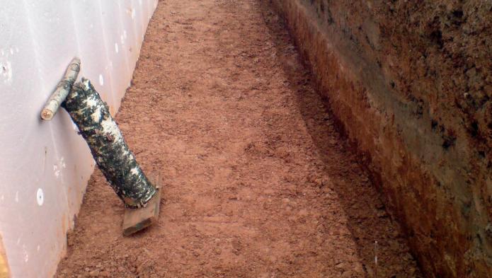 Самодельная толкушка и глина в котловане у стены погреба