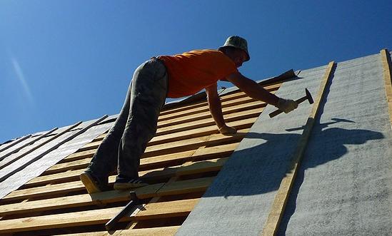 Строитель закрывает крышу листами гидроизоляционного материала