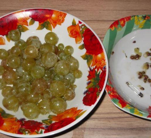 Ягоды белого винограда и виноградные косточки в отдельных тарелках на столе