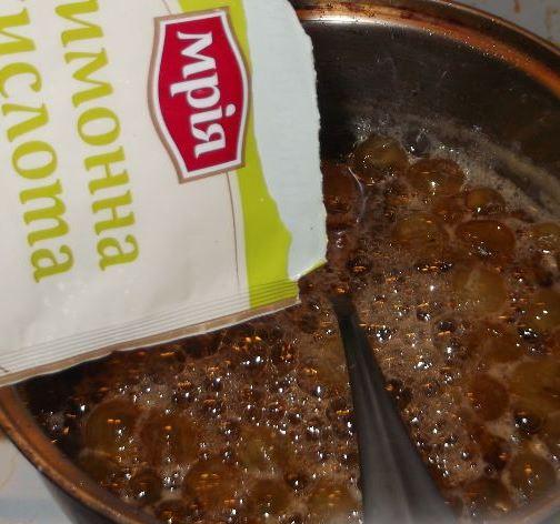 Виноградное варенье в кастрюле с ложкой и пакетик с лимонной кислотой